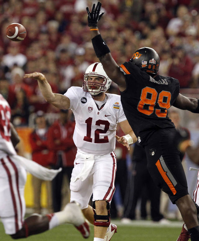 Stanford quarterback Andrew Luck (12) throws under pressure from Oklahoma State defensive tackle Nigel Nicholas (89) during the first half of the Fiesta Bowl NCAA college football game Monday, Jan. 2, 2012, in Glendale, Ariz. (AP Photo/Ross D. Franklin)