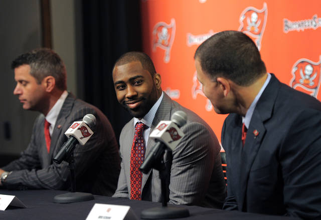 Tampa Bay Buccaneers general manager Mark Dominik, left, cornerback Darrelle Revis, center, and head coach Greg Schiano address the media while announcing that the Buccaneers have acquired Revis from the New York Jets during an NFL press conference Monday, April, 22, 2013, in Tampa, Fla. The Buccaneers and Revis have agreed on a six-year contract. (AP Photo/Brian Blanco)