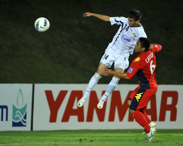 Bunyodkor's Alibobo Rakhmatullev sends the ball into the net scoring the goal, as Adelaide United's Cassio, bottom, tries to stop him during their 2012 AFC Champions League quarter-final second leg match in Tashkent, Uzbekistan, Wednesday, Oct. 3, 2012. (AP Photo/Anvar Ilyasov)