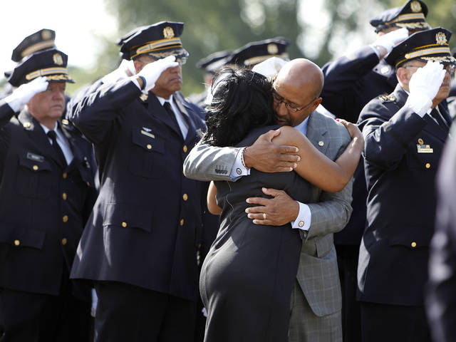 Mayor Michael Nutter, second from right, hugs Wayne Lipscomb, mother of fallen Philadelphia police officer Moses Walker, before the viewing in Philadelphia Sunday Aug. 26, 2012. Officer Walker was shot and killed walking to the bus after his shift last Saturday morning. ( AP Photo/Philadelphia Daily News, DAVID MAIALETTI)