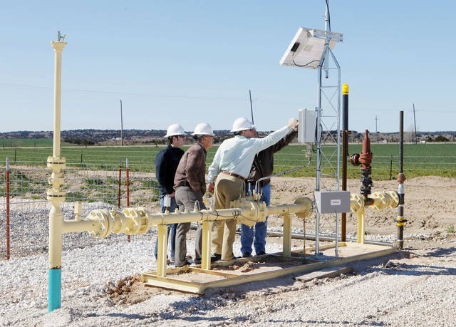 Continental Resources officials check a gas meter Friday on the site of the state's first cross-unit well near Watonga.