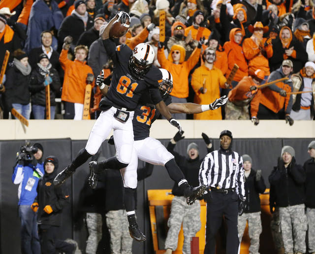 Oklahoma State wide receiver Jhajuan Seales (81) celebrates his touchdown against Baylor with teammate Jeremy Smith (31) in the fourth quarter of an NCAA college football game in Stillwater, Okla., Saturday, Nov. 23, 2013. Oklahoma State won 49-17. (AP Photo/Sue Ogrocki)
