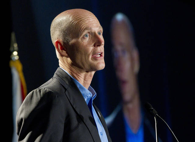 FILE - In this May 16, 2012, file photo Florida Gov. Rick Scott speaks in Fort Lauderdale, Fla. In a victory for Republicans, the federal government has agreed to let Florida use a law enforcement database to challenge people's right to vote if they are suspected of not being U.S. citizens. The agreement, made in a letter Scott's administration that was obtained by The Associated Press, grants the state access to a list of resident non citizens maintained by the Department of Homeland Security. The Obama administration had denied Florida's request for months. (AP Photo/J Pat Carter, File)