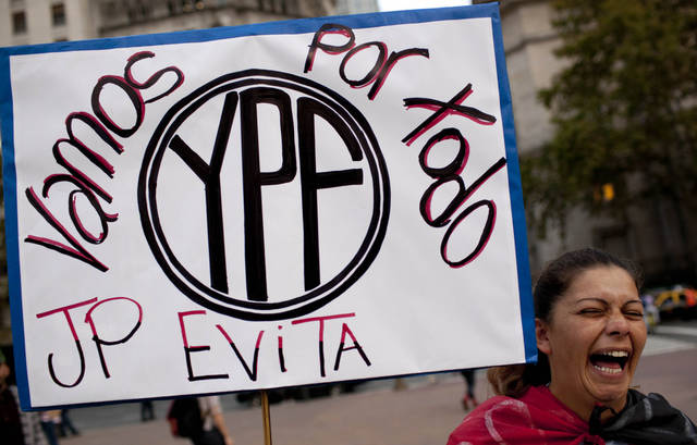 "A woman holds up a banner that reads in Spanish ""We are going for all YPF"" during a demonstration in support of a bill proposed by Argentina's President Cristina Fernandez outside the government house in Buenos Aires, Argentina, Monday, April 16, 2012. Fernandez on Monday proposed a bill to expropriate 51 percent of the shares of YPF oil company that is controlled by Spain's Repsol, moving ahead with the plan despite fierce opposition from Madrid. (AP Photo/Natacha Pisarenko)"