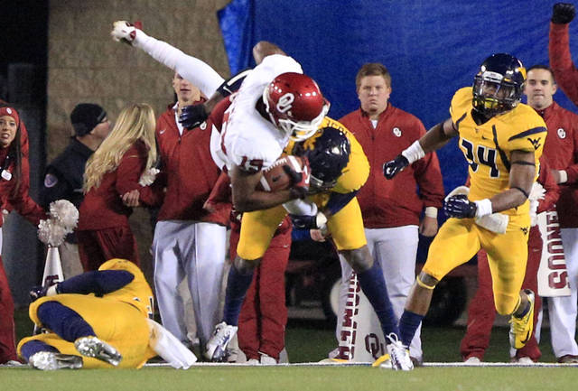West Virginia's Karl Joseph (8) tackles Oklahoma's Justin Brown (19) during the fourth quarter of their NCAA college football game in Morgantown, W.Va., on Saturday, Nov. 17, 2012. Oklahoma won 50-49.(AP Photo/Christopher Jackson)