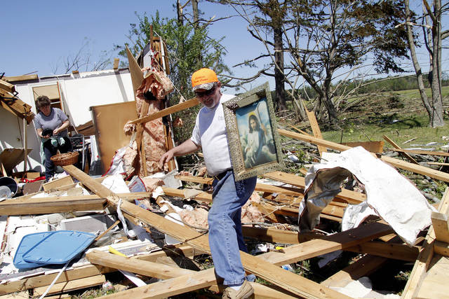 Robert Byrum, right, cleans up his father home in Askewville , N.C., Sunday after a tornado moved through the area Saturday. Rescue crews searched for survivors in wind-blasted landscapes Sunday in North Carolina, the state hardest hit by a storm system that spawned dozens of tornadoes from Oklahoma to Virginia and left dozens dead. (AP Photo/Jim R. Bounds)