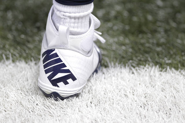 This Dec. 16, 2012 photo shows a Nike shoe worn by a St. Louis Rams football player during the first quarter of an NFL football game between the St. Louis Rams and the Minnesota Vikings in St. Louis. Strong demand in North America helped Nike post second-quarter net income that beat expectations Thursday, Dec. 20, 2012, despite weaker sales in China and costs related to the sale of two brands. (AP Photo/Seth Perlman)