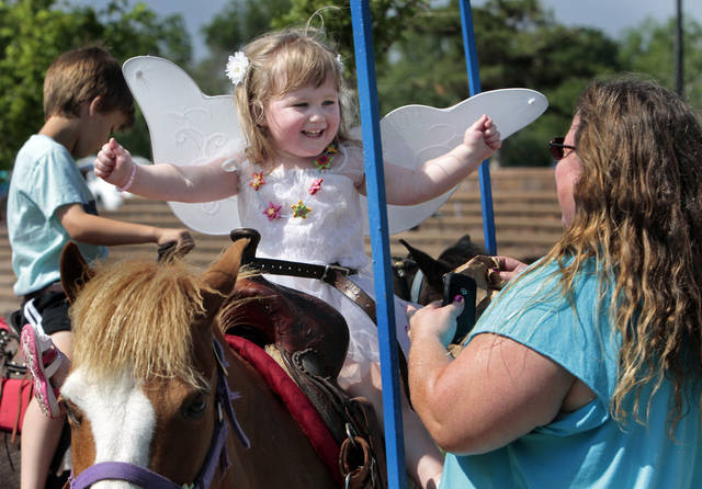 Lilly Haider, 2, rides a pony at the annual May Fair Festival on Saturday at Andrews Park in Norman, while Sharon Lee watches. PHOTOS BY STEVE SISNEY, THE OKLAHOMAN