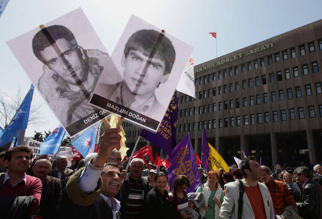 A man holds posters of a Turkish, Deniz Gezmis, left, and a Kurdish youth, as thousands of people protest against Turkey's 1980 coup outside a courthouse in Ankara, Turkey, Wednesday, April 4, 2012. Thousands of protesters and family members of victims gathered outside the court as an Ankara court began hearing the case against two surviving coup leaders, retired army chief Kenan Evren, 94, and former Air Force commander Tahsin Sahinkaya, 87. The two surviving coup leaders, both in poor health, have been hospitalized and did not attend.(AP Photo/Burhan Ozbilici)