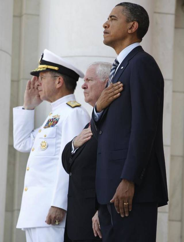 "President Barack Obama, Defense Secretary Robert Gates, center, and Chairman of the Joint Chiefs of Staff Adm. Michael Mullen, left, are listen to the playing of ""Taps"" during a Memorial Day ceremony at Arlington National Cemetery, Monday, May 30, 2011. (AP Photo/Charles Dharapak) ORG XMIT: WHCD108"