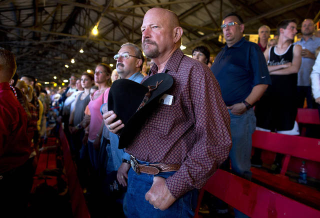 Spectators stand as the U.S. flag is paraded around the rodeo arena before the start of the Prescott Frontier Days Rodeo, Wednesday, July 3, 2013 in Prescott, Ariz. A mile-high city about 90 miles northwest of Phoenix, Prescott remains a modern-day outpost of the pioneer spirit. It's that spirit that will guide officials as they navigate the days ahead and figure out how to honor the elite Hotshot firefighters who died in a nearby wind-driven wildfire that is still burning. (AP Photo/Julie Jacobson)