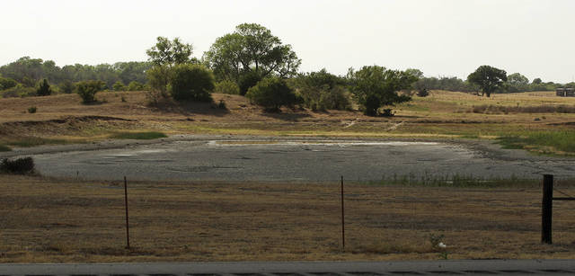 In this Wednesday, July 18, 2012 photo, a nearly empty farm pond is pictured near Watonga, Okla. The nation's widest drought in decades is spreading, with more than half of the continental United States now in some stage of drought and most of the rest enduring abnormally dry conditions. (AP Photo/Sue Ogrocki)