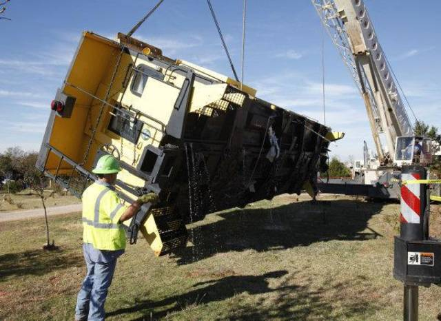 Cranes upright two tornado toppled train cabooses as they are lifted back onto their tracks at the Red Rooster Inn, west of Piedmont, OK, Friday, Nov. 4, 2011. By Paul Hellstern, The Oklahoman ORG XMIT: KOD