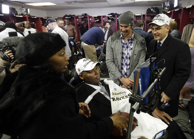 In this Sunday, Jan. 20, 2013 photo, former Baltimore Ravens NFL player O.J. Brigance, center, his wife Chanda, left, and former Olympic swimmer Michael Phelps, second from right, visit the Ravens locker room after the NFL football AFC Championship football game against the New England Patriots in Foxborough, Mass. Confined to a wheelchair as he battles Amyotrophic Lateral Sclerosis, the former Baltimore linebacker presented the Lamar Hunt trophy to the team after it beat the New England Patriots 28-13.  (AP Photo/Elise Amendola)