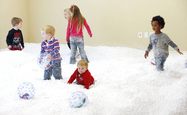 Children play in the artificial snow made from styrofoam pieces Monday at Snowplace Like The Mac at the Multi-Activity Center in Edmond. PHOTO BY DAVID MCDANIEL, THE OKLAHOMAN