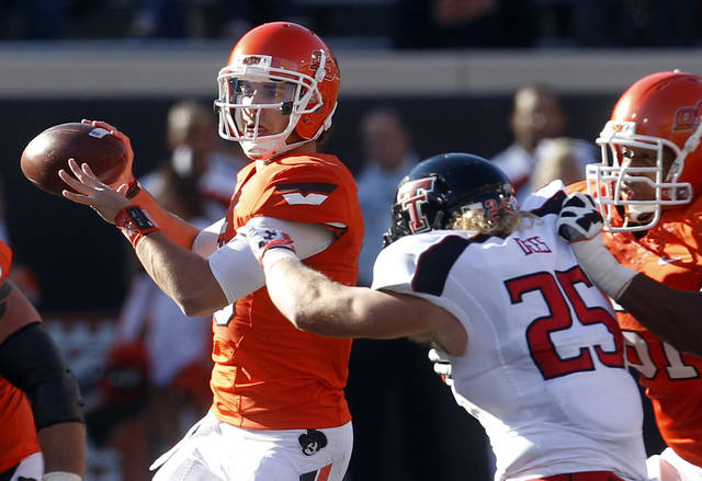 Oklahoma State quarterback Clint Chelf, left, passes under pressure from Texas Tech linebacker Blake Dees (25) as Oklahoma State offensive lineman Brandon Webb (51) blocks in the first quarter of an NCAA college football game in Stillwater, Okla., Saturday, Nov. 17, 2012. (AP Photo/Sue Ogrocki)
