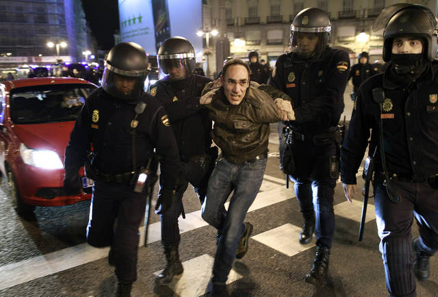 Riot police detain a protestor during a demonstration against corruption in Madrid, Spain, Saturday, Feb. 2, 2013. Spain's prime minister promised Saturday to publicly disclose the amount of funds in all his personal bank accounts, denying recent media reports that allege he and members of his governing Popular Party accepted or made under-the-table payments. (AP Photo/Andres Kudacki)