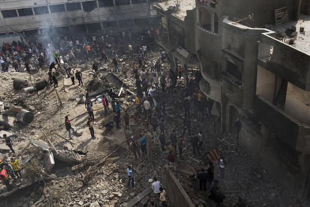 Palestinians inspect the damage of an Israeli forces strike in Gaza City, Sunday, Nov. 18, 2012. The Israeli military widened its range of targets in the Gaza Strip on Sunday to include the media operations of the Palestinian territory's Hamas rulers, sending its aircraft to attack two buildings used by both Hamas and foreign media outlets. (AP Photo/Bernat Armangue)
