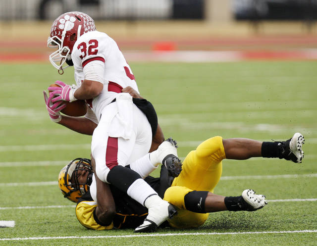 Lawton MacArthur's Anthony Burris (7) tackles Tray Fish (32) of Ardmore during a high school football playoff Class 5A semifinal game between Lawton MacArthur and Ardmore in Yukon, Okla., Saturday, Nov. 26, 2011. Photo by Nate Billings, The Oklahoman