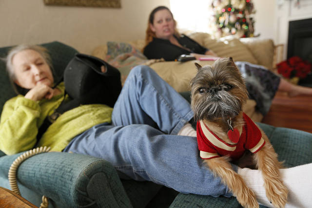 Trevor, a Brussels Griffon, sits on the leg of his owner, resident Cathi Doar, left, next to manager Lisa Schrameck  in the common area at Green Acres, 7601 SW 74. <strong>NATE BILLINGS - The Oklahoman</strong>