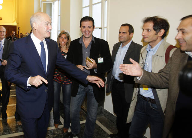 Greek Prime Minister George Papandreou jokes with the Greek journalists as he takes a short break during an emergency meeting at the Greek parliament in Athens, on Thursday, Nov. 3, 2011. A spokesman for Greece's government says it is prepared to discuss an opposition demand for the creation of a transitional government to approve the latest European bailout deal and secure the next installment of rescue loans for the country. (AP Photo/Thanassis Stavrakis) ORG XMIT: XTS114