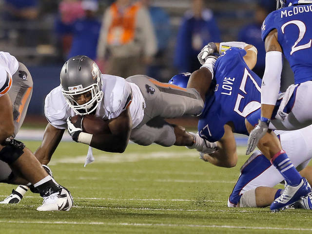 Oklahoma State's Joseph Randle (1) dives forward as he is brought down by Kansas' Jake Love (57) during the college football game between Oklahoma State University (OSU) and the University of Kansas (KU) at Memorial Stadium in Lawrence, Kan., Saturday, Oct. 13, 2012. Photo by Sarah Phipps, The Oklahoman