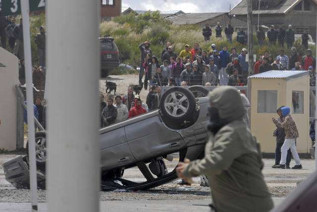 An car sits overturned in the parking area of a supermarket during looting in San Carlos de Bariloche, about 1.630 km southwest of Buenos Aires, Argentina, Thursday, Dec. 20, 2012. Hooded people looted at least three supermarkets and set a car on fire after claiming for food to celebrate Christmas in the city of Bariloche, part of Argentina's Patagonia region. (AP Photo/Diario Rio Negro)