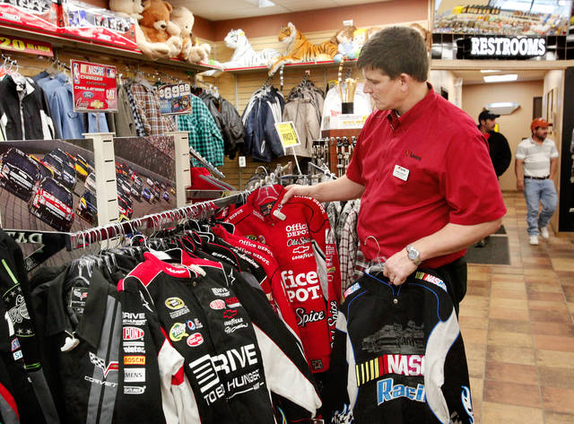 RETAIL GIFT SALES / I-35: Shaun Andrews, general manager of the Pauls Valley store, adds additional racing jackets to a clothes rack. The recently opened Love's Travel Plaza on Interstate 35 in  Pauls Valley offers motorists and customers an expanded selection of items for sale inside the store. This travel center center stocks many items that usually aren't found in travel stores along the highways. Photo taken Tuesday, Dec. 20, 2011.  Photo by Jim Beckel, The Oklahoman