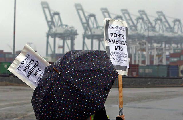 A clerical worker pickets in the rain at the Maersk cargo terminal, where container-handling cranes are in the up and idle position, background, at the Port of Los Angeles Thursday, Nov. 29, 2012.  Cargo ships were stacking up at the ports of Los Angeles and Long Beach as a strike by about about 70 clerical workers shut down most of the terminals that together are the nation's busiest port complex.  Dockworkers were refusing to cross the picket lines even though an arbitrator ruled the walkout invalid on Tuesday.  By Thursday morning, at least 18 ships docked and inside the adjacent harbors were not being serviced, port spokesmen said. (AP Photo/Nick Ut)