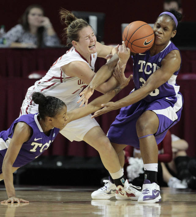 Oklahoma Sooners' Whitney Hand (25) is fouled while guarded by TCU Horned Frogs' Briesha Wynn (right) and Antoinette Thompson as the University of Oklahoma (OU) Sooners play the Texas Christian University (TCU) Horned Frogs in women's college basketball at the Lloyd Noble Center on Wednesday, Dec. 28, 2011, in Norman, Okla.  