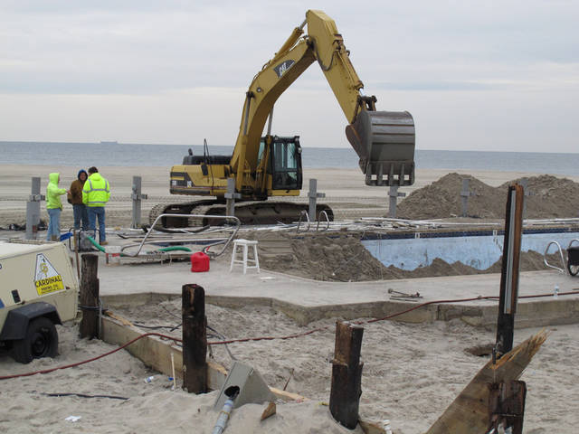 Work crews scoop sand from a beachfront swimming pool in Sea Bright N.J. on Jan. 15, 2013 as the town's cleanup from Superstorm Sandy continued. The town's entire business district was wiped out (four shops have since re-opened) and 75 percent of residents are still homeless. Yet Sea Bright is determined to rebuild as a debate rages on whether to restore shore communities to their pre-storm condition, or buy out properties in flood-prone areas and depopulate them. (AP Photo/Wayne Parry)