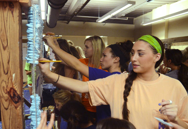 Alpha Chi Omega member Emily Gose, right, pomps a panel in preparation for her house�s homecoming  decoration at Oklahoma State University. Photo by Adam Kemp, The Oklahoman