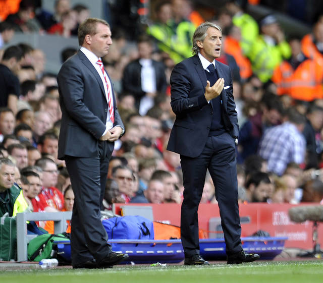 Liverpool's manager Brendan Rodgers, left and Manchester City's manager Roberto Mancini, right, during their English Premier League soccer match at Anfield in Liverpool, England, Sunday Aug. 26, 2012. (AP Photo/Clint Hughes)