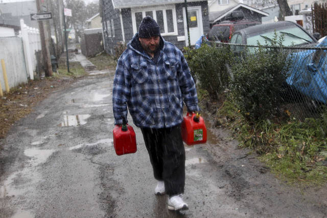 Joe Graham delivers some gas in the snow to a neighbor for use in her generator in the New Dorp section of Staten Island, N.Y. Wednesday, Nov. 7, 2012.  A nor'easter blustered into New York and New Jersey on Wednesday, threatening to swamp homes all over again, plunge neighborhoods back into darkness and inflict more misery on tens of thousands of people still reeling from Superstorm Sandy.  (AP Photo/Seth Wenig) ORG XMIT: NYSW107