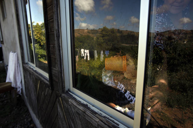 In this photo taken Nov. 29, 2012, the son of Evelyn Perez looks out the window of their home, in Navidad, Chile. The motion of the tectonic plates that are responsible for the big earthquakes that occur in Chile are also responsible for the beautiful mountains, active volcanoes, and a range of climates - from very cold to deserts, says Paul Caruso, a geophysicist with the United States Geological Service, making Chile a fascinating place. (AP Photo/Luis Hidalgo)