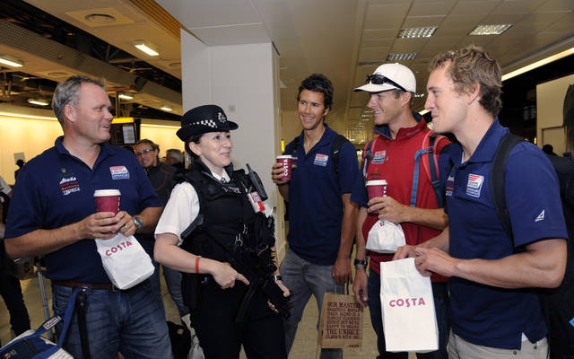 A British police officer speaks with members of the U.S. Olympic sailing team following their arrival at Heathrow Airport in London, Monday, July 16, 2012. Heathrow is set to welcome a record number of passengers Monday as athletes begin arriving for the London Olympics. (AP Photo) UNITED KINGDOM OUT, NO SALES, NO INTERNET, NO MAGS