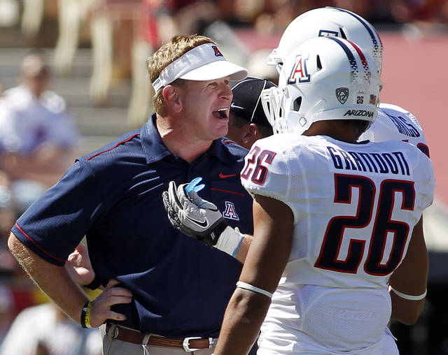 Arizona coach Mike Stoops, left, yells at Jourdon Grandon (26) and Derek Earls, rear, during the first half of an NCAA college football game against Southern California on Saturday, Oct. 1, 2011, in Los Angeles. USC won 48-41. (AP Photo/Danny Moloshok) ORG XMIT: CADM115