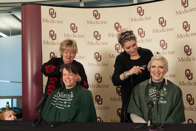 Above and left: Cathy Rogers, with Heads Above Salon at the Stephenson Cancer Center, and Mary Timme, with Tonic the Salon, shave Dr. Rene McNall-Knapp and TeNeil Spaeth's heads Friday during a news conference.