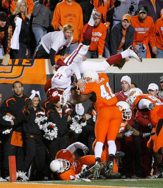 OU quarterback Sam Bradford is flipped in the air after a hitting OSU's Orie Lemon (41) during the second half of the college football game between the University of Oklahoma Sooners (OU) and Oklahoma State University Cowboys (OSU) at Boone Pickens Stadium on Saturday, Nov. 29, 2008, in Stillwater, Okla. STAFF PHOTO BY CHRIS LANDSBERGER