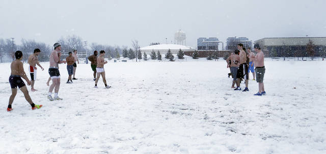 A group of students play a game in football in the snow at the University of Central Oklahoma in Edmond, Okla., Tuesday, Feb. 12, 2013.Photo by Sarah Phipps, The Oklahoman