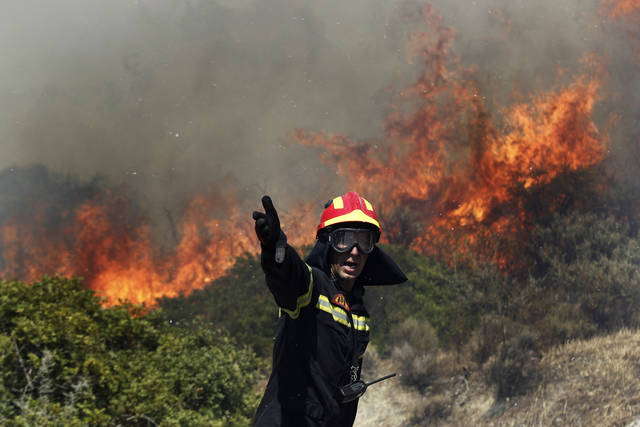 A firefighter gestures instructions to his colleagues as a fire rages in Palea Fokaia, south of Athens, Saturday, June 16, 2012. A fire aided by strong winds has burned grassland and threatened houses near the town of Keratea, 50 kilometers (30 miles) south of Athens. The fire started in the early Saturday afternoon on dried grass, apparently as the result of an accident and has been spreading fast, threatening to engulf isolated houses on the outskirts of the towns of Keratea and Palea Fokaia. (AP Photo/Kostas Tsironis)
