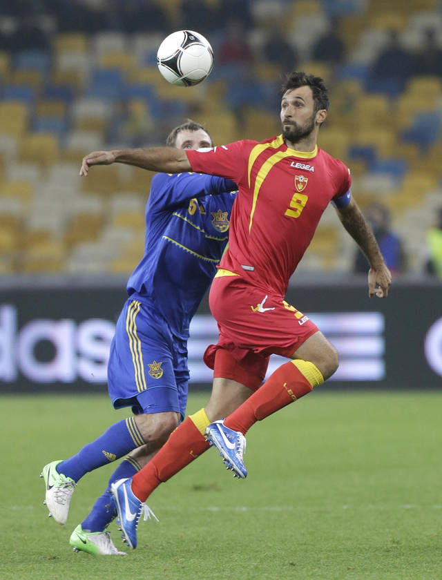 Olexandr Kucher, left, of Ukraine vies for the ball with Mirko Vucinic of Montenegro during a World Cup 2014 Group qualification soccer match in Kiev, Ukraine, on Tuesday. Oct. 16, 2012.(AP Photo/Efrem Lukatsky)