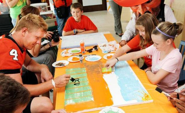 OSU's Brandon Weeden, left, works on a painting with cancer patient Hope Dollarhide, 11, lower right in pink shirt, and cancer survivor Morgan Snowden, 9, upper right in orange shirt, as mascot Pistol Pete and Austin Snowden, 10, Morgan's brother, watch during a visit by  OSU football players to the Jimmy Everest Center for Cancer and Blood Disorders in Children in Oklahoma City, Wednesday, July 14, 2010. Photo by Nate Billings, The Oklahoman