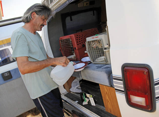 Vin Bayne pours water for his pets while waiting at a gas station at Hwy 9 and SE 108 Ave. after evacuating his home as a wildfire burns through Cleveland County near Norman, Okla., Friday, Aug. 3, 2012. Vin Bayne and his wife Polly Bayne evacuated their home off of SE 132nd with their 4 cats and 2 dogs. Photo by Nate Billings, The Oklahoman
