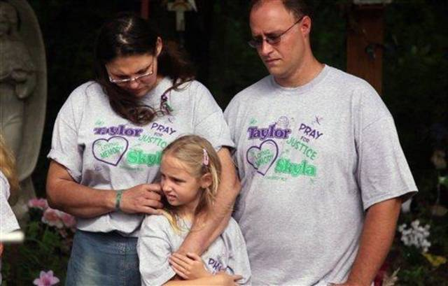 From left, Rose Whitaker, Jayme Whitaker, 8, and William Whitaker comfort each other during a news conference held at the site where their daughter, Skyla Jade Whitaker, 11, and her friend, Taylor Paschal-Placker, 13, were killed on a country road just north of Weleetka, Okla., Tuesday, June 8, 2010. The girls were found shot to death on June 8, 2008, along a dirt road near Weleetka. (AP Photo/Tulsa World, Adam Wisneski)