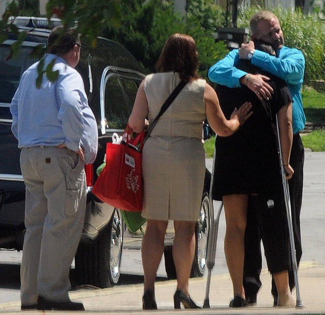 Samantha Yowler, right, is comforted by relatives Friday, July 27, 2012, at Maiden Lane Church of God in Springfield, Ohio. Yowler, a Graham High School graduate, was shot in the leg on Friday, July 20, in Aurora, Colo., as her boyfriend, Springfield native Matt McQuinn shielded her from the gunman. McQuinn was one of 12 who died in the shooting, which injured 58. (AP Photo/Springfield News-Sun, Marshall Gorby)