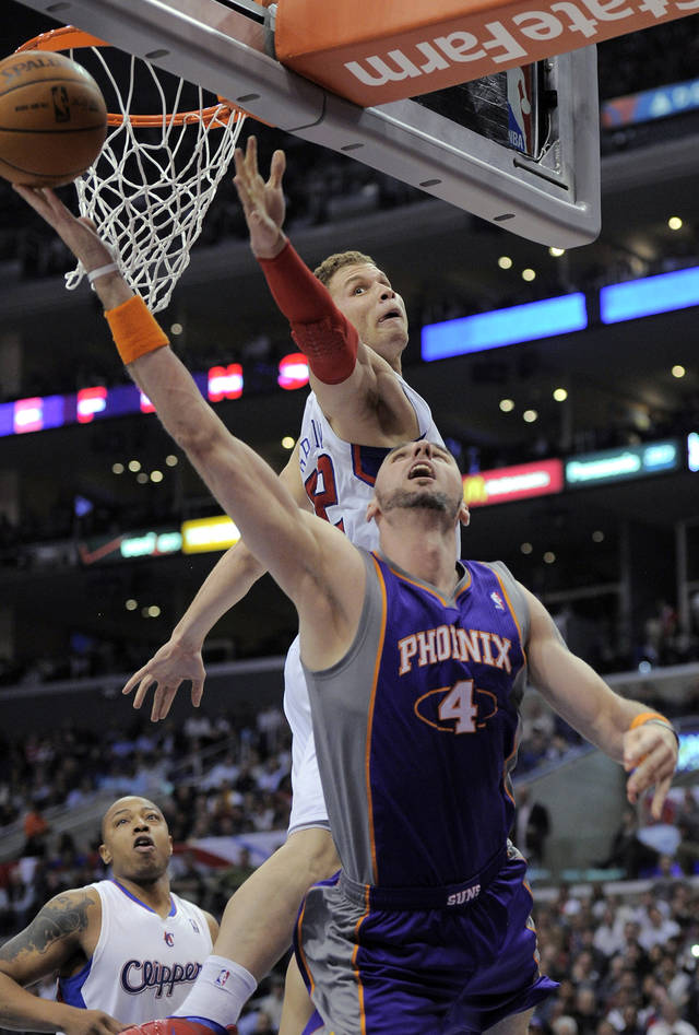 Phoenix Suns center Marcin Gortat (4), of Poland goes up for a shot as Los Angeles Clippers forward Blake Griffin defends during the first half of an NBA basketball game, Wednesday, March 28, 2012, in Los Angeles. (AP Photo/Mark J. Terrill)