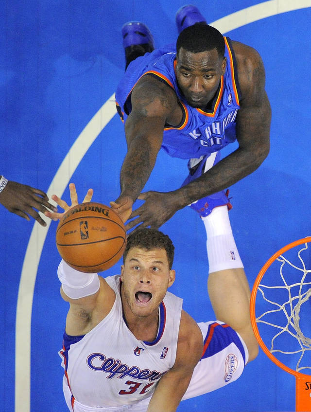 Los Angeles Clippers forward Blake Griffin, below, goes after a rebound along with Oklahoma City Thunder center Kendrick Perkins during the first half of their NBA basketball game, Tuesday, Jan. 22, 2013, in Los Angeles.  (AP Photo/Mark J. Terrill)  ORG XMIT: LAS105