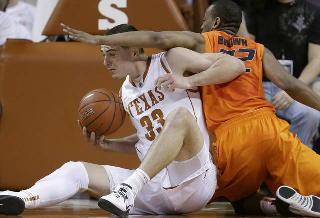 Texas&#039; Ioannis Papapetrou (33) and Oklahoma State&#039;s Markel Brown, right, scramble for a loose ball during the first half of an NCAA college basketball game, Saturday, Feb. 9, 2013, in Austin, Texas. (AP Photo/Eric Gay) ORG XMIT: TXEG105