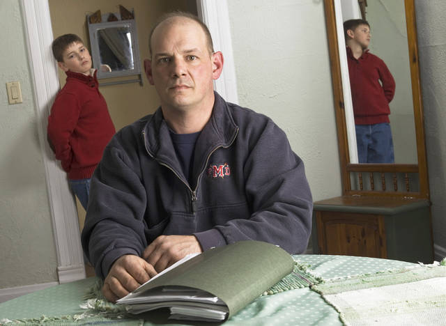 Terry Becker and his 10-year-old son Nate are shown in their Milton, Wis., home. Terry Becker says he racked up $25,000 in medical debt for the boy which has left him with bad credit. AP Photo